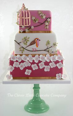 Bird and blossoms Wedding Cake, Dark pink bottom tier, white middle tier and a light pink top tier.  Painted birds, white flowers, gold bird cage