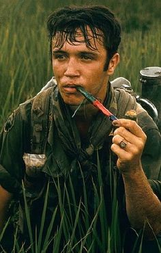 A US soldier from the 9th Division smokes a long pipe whilst sitting in long grass, 1968.
