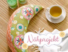 """Yogakissen in Halbmondform neben Tee und Kerzen + Banner """"Nähprojekt"""""""