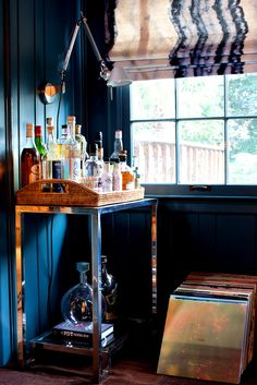 Wood and metallic bar cart in dark teal room with fabric blinds on window