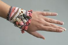 Unique handmade crochet cuff in cream, pale pink and burgundy, decorated with crochet roses and Baltic amber and glass beads. It is buttoned by 2