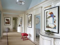 A hallway is decorated with artworks by Walton Ford and cabinets by Maya.