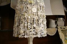 A box of white buttons makes such a sweet, delicate looking lampshade. #quilting #sewing #buttons