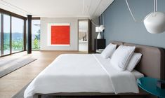 A monochrome bedroom palette is punctuated by saturated orange artwork.