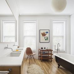 A bathroom in Brent Allen Buck's Brooklyn brownstone with midcentury furnishings and sleek fixtures to compliment the more traditional clawfoot tub. Click through for more images of this Brooklyn renovation.