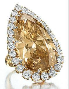The Burton Cognac Diamond Ring || Coloured diamond ring by Van Cleef & Arpels. 1974 _ Set with a modified pear-shaped fancy deep brownish orangy yellow diamond, weighing approximately 32.14 carats, within a circular-cut diamond surround, the shoulders decorated with circular-cut diamonds, mounted in gold-topped platinum, circa 1974, with maker's mark Signed Van Cleef & Arpels.