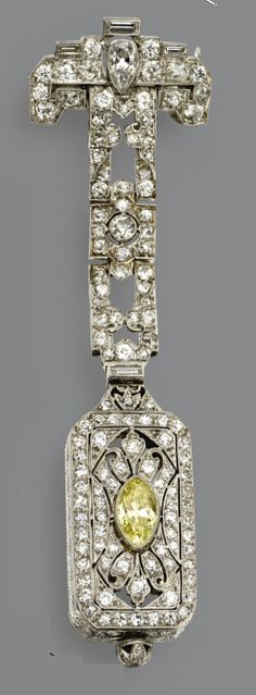 An Art Deco platinum and diamond lapel watch, circa 1920. The openwork rectangular case and articulated surmount set with old European-cut, single-cut, baguette and pear-shaped diamonds weighing approximately 2.40 carats, the centre of the case accented with a marquise-shaped diamond of yellow colour weighing approximately .60 carat, the dial applied with black Arabic numerals and blued steel hands, movement signed Longines W. Co., Swiss. #Longines #ArtDeco #watch