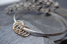 Sterling silver bangle with five gold rings £95.00