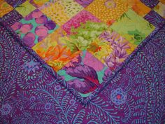 SUNNY-SIDE-UP! Quilt --Another Kaffe Fassett inspired quilt. This quilt is made from both new and out of production fabrics, designed by Kaffe Fassett, Phillip Jacobs, Brandon Mabley and Martha Negley. This is the perfect gift for anyone who loves the combination of purples, yellows, oranges and greens. The backing fabric is made of Kaffe Fassetts Ferns Fabric in Purple. This quilt measures 70 x 70 inches. PROFESSIONAL Machine quilting was done by the award winning quilter and friend, Tammy…