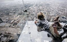 Stand on the glass balcony of the Willis Tower in Chicago