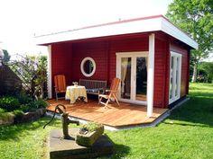 Gartenhaus-Idylle in modernem Stil: Dieses schicke Gartenhaus mit Terrasse bezaubert durch sein Rundfenster und den Anstrich in Schwedenrot und Weiß. Gepflegte Beete und ein kleiner Brunnen machen die Idylle perfekt.