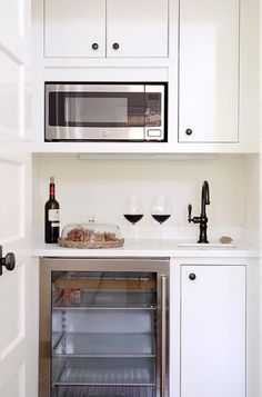 Small, chic butler's pantry features creamy white inset cabinets adorned with br… Small, chic butler's pantry features creamy white inset cabinets adorned with bronze knobs fitted with an over the counter microwave. - Own Kitchen Pantry Mini Kitchen, Kitchen Pantry, New Kitchen, Compact Kitchen, Kitchen Small, Studio Decor, Basement Kitchenette, Inset Cabinets, Coffee Nook