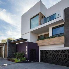Casa com fachada branca, madeira, portão preto e detalhe roxo/lilás.