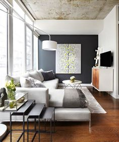 A narrow living room uses modern furniture to fit cozy accessories... mesitas que se guarden en el mismo espacio