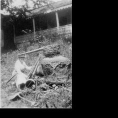 """On back of image: ""This is a real copper still. Has been cut up by the marshals.""; a woman sitting beside the copper still with an ax in her hand and surrounded by other tools and tall grass, house behind her"" - Kentucky Digital Library"