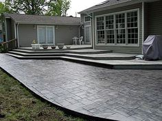 The concrete was stamped with an Ashlar slate pattern and colored using light grey hardener with a charcoal release.