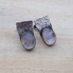 Jewels by KT: Delikatne, nieco surowe kolczyki wykonane od podstaw tradycyjnymi technikami jubilerskimi ze srebra i niewielkich kaboszonów kamienia księżycowego. Pięknie mienią się niebieskim blaskiem.  Srebro oksydowane (przyciemniane), młotkowane i polerowane.