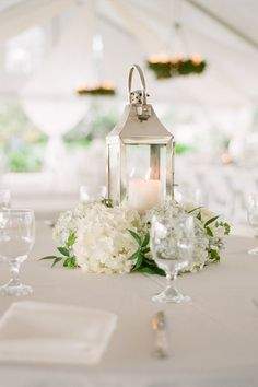 love this silver lantern centerpiece with lush flowers at the base