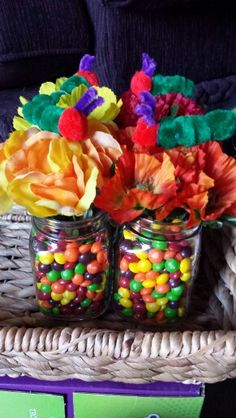 Very hungry caterpillar centerpieces: Mason jars, fake flowers, skittles, and a caterpillar made from pom poms.