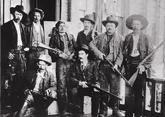 """The most dangerous outlaw in Indian Territory,"" Ned Christie was shot to death in 1892. His body was placed on a board (back row, third from left), while U.S. deputy marshals posed with their ""prize"" and their 1873 and 1886 Winchester lever-action rifles—along with one trapdoor Springfield single-shot rifle. Christie holds his .44-40, 1873 Winchester for the last time."