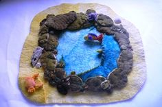 Rock pool scene, made of wool felt with tiny sea creatures ,on the rock ledge is an octopus.