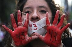 A woman holds up her red-painted hands and the number 43 written on them to remember the 43 missing students from the Isidro Burgos rural teachers college during a protest in Mexico City, Friday, Dec. 26, 2014. Protesters marched through the city to mark the three months since the 43 students were taken by municipal police and then handed over to a drug gang to be killed and then the bodies burned, according to the results of the Attorney General's investigation. (AP Photo/Marco Ugarte)