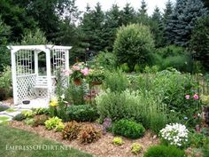 20+ Ways to create vertical interest in the garden with arbors, trellis, obelisks, and more. White arbor in flower garden with seating area.