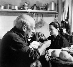 "Pablo Picasso, his dog, ""Lump,"" and Jacqueline Roque. Photographed by David Douglas Duncan, Cannes, 1957."