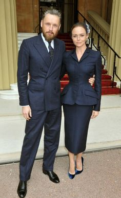Now this is tailoring! Fashion designer Stella McCartney, received her OBE in a bespoke blue suit by her own label, topped off with a vintage Cartier brooch, worn with a veil, as a headpiece. She was accompanied by her husband, Alasdhair Willis. I wonder what foundation garments she's wearing.