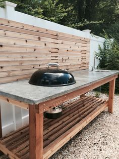 Cedar wood outdoor kitchen with a concrete countertop and built in Weber charcoal grill and sink.