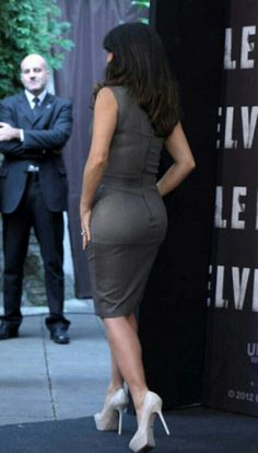 Salma Hayek curves in a figure hugging sleeveless gray dress with off white platform pumps