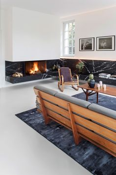 Nero Marquina marble is used in multiple rooms. In the living room, a strip of stone defines a bench that wraps around the space. Both the sofa and armchair are vintage.
