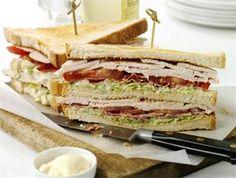 Klassieke Club Sandwich - Benodigdheden per Club Sandwich: * 3 sneden wit casinobrood * sla * mayonaise * peper en zout * 1 plak belegen kaas * 1 plak kiprollade * 1 tomaat * plakjes spek (dungesneden) * 1 ei * mini-augurkjes * cocktailprikkers