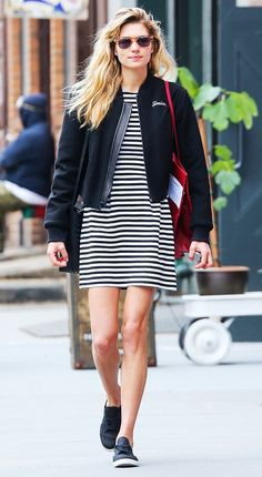 Model Jessica Hart wears a personalized bomber jacket with a black and white striped dress and easy black sneakers