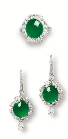 JADEITE AND DIAMOND RING AND PAIR OF MATCHING PENDENT EARRINGS Centring on a translucent oval jadeite cabochon of bright emerald green colour, surrounded by pear-shaped diamonds together weighing approximately 2.50 carats; and pair of pendent earrings of matching colour and translucency, set with pear-shaped and brilliant-cut diamonds