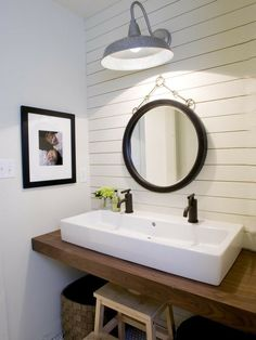 Coastal powder room design with paneled accent wall, chunky wood floating bathroom vanity, rectangular white porcelain sink, woven baskets and black convex mirror.