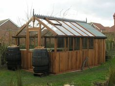 Light brown stained western red cedar greenhouse with rain barrels