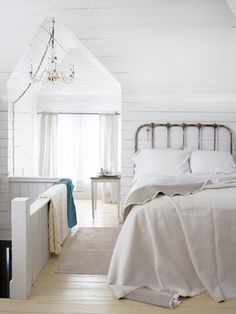 White bedroom. looks like an attic with dormer window. gorgeous.