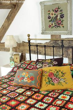 Colourful Handmade Crochet Throw and Floral Cushions add cosiness to the Bedroom: www.vintage-home.co.uk