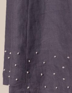 French knot detail on skirt, dress, or shirt.