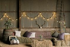 Hay bale couches, wine barrel table ends, plaid accents, and antler and ladder décor make this industrial barn lounge area a rustic dream.