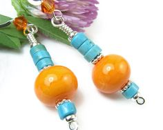 These eye-catching orange and blue dangle earrings are made with bright lampwork glass rondelles, turquoise-colored howlite, sparkly Swarovski