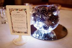 Our centrepieces were goldfish bowl vases filled with pine cones (kindly collected from Norfolk woods by friends of the family on their dog-walks!) and battery operated fairy lights - they looked lovely in the low-lit barn. We also made our own menu cards and table numbers using the double-sided Tolsby frames from Ikea...""