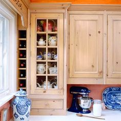Plates On View: Take advantage of glass-front cabinets to display treasured pieces of china. Teapots fill this small cupboard with color and shape.