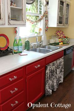 I like the red Kitchen Cabinets .... But I don't get the chipping old-looking top cabinets. They don't go with the shiny red bottom cabinets.