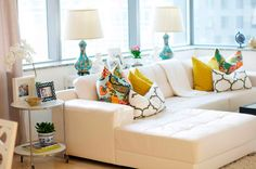 home of interior designer caitlin wilson - white sectional with colorful pillows. LOVE IT ALL!