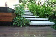 Na área da piscina, o arquiteto criou um deque de madeira ipê e utilizou lajes de concreto com cimento queimado branco, sustentadas por pilares pintados de preto, para formar uma escada. O recurso permite que os degraus pareçam suspensos Foto: Raul Hilgert, divulgação