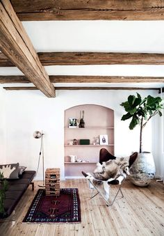 Loooove this mix- the exposed beams, accent built-in, butterfly chair and dark leather
