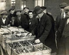 Een ambtenaar van de Keuringsdienst van Waren (met hoed) keurt fruit, dat in bakken ligt. Om hem heen staat een groepje lachende mannen/verkopers die allen een pet op hebben. [Amsterdam],1926.