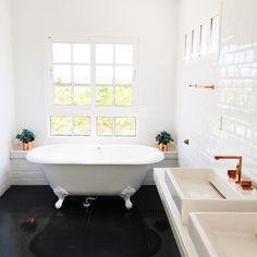 Inspiração de banheiro da Casa Depois dos Quinze, de Bruna Vieira. Banheira vitoriana e pias em rosé gold, banheiro bem clean com folhas para decorar.